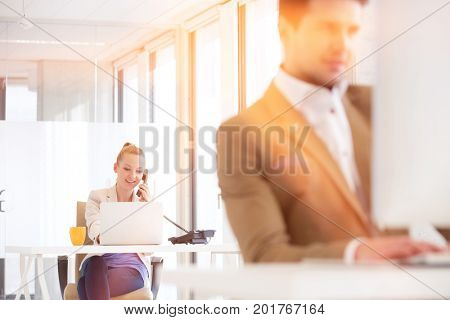 Young businessman using landline phone with male colleague in foreground at office