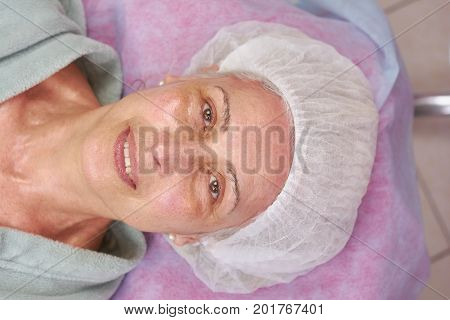 Mature beauty clinic patient smiling. Happy female face top view. Quality health services.