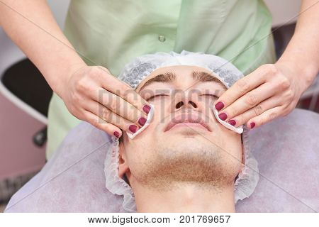 Cosmetician cleaning face, cotton pads. Young man in beauty clinic. Facial toners for dry skin.