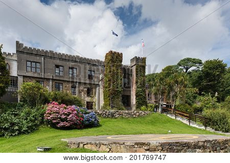 Clifden Ireland - August 4 2017: The historic gray and brown stone castle of the town is now an upscale hotel. Ivy on the walls in flower setting on hill with forest against blue sky with white clouds.