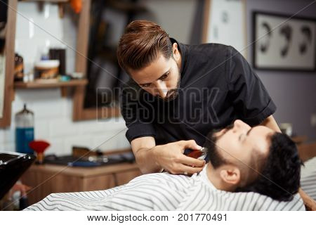 Back view of hairstylist in black uniform working at barber shop caring about face of client and cutting bread for young man. Male who sitting at chair and looking up. Handsome stylist doing haircut.
