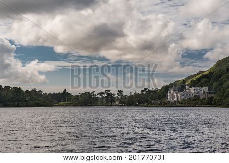 Connemara Ireland - August 4 2017: Twilight photo of Kylemore Abbey seen from dam of Pollacapall Lough. Gray building is in distance against green forested hills and under heavy cloudscape.
