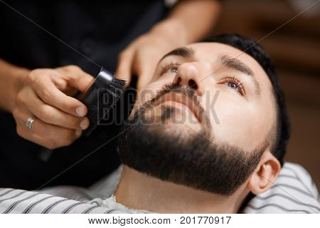 Close up of young brunet man visiting   barbershop, relaxing and lying at chair. Hairstylist comb out and cutting bread for client at beauty salon only for man.