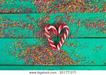 Christmas cane in a heart shape and color sprinkling on turquoise wooden background
