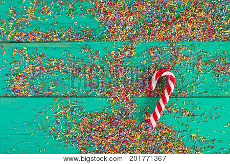 Christmas background. Christmas canes Color sprinkling on turquoise wooden background