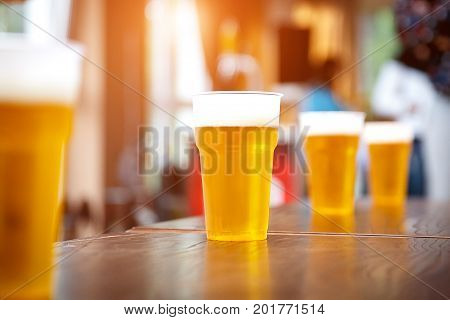 A row of plastic beer glasses with a light beer on a party