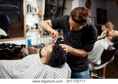 Back view of handsome hairdresser cutting bread for brunet man in modern barbershop. Stylist in black doing correction with thread. Beauty salon only for man.