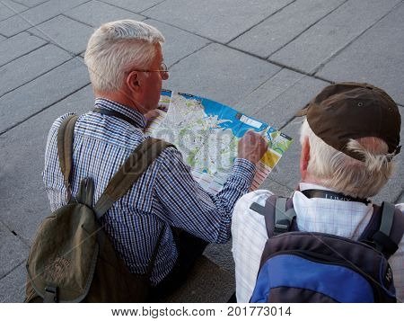 TALLINN, ESTONIA - JUNE 10, 2017: Mature tourists with city plan at the Town Hall. The Old Town is one of the best preserved medieval cities in Europe and is listed as a UNESCO World Heritage Site