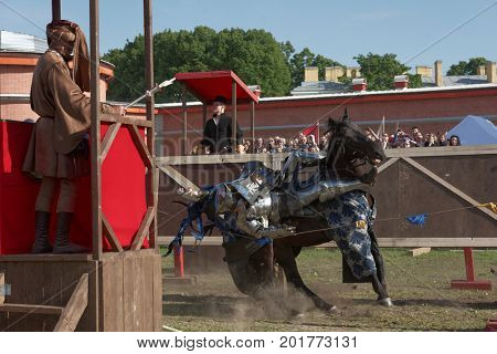 ST. PETERSBURG, RUSSIA - JULY 9, 2017: Armored knight falls off a horse in the jousting tournament during the military history project Battle On Neva at St. Peter and Paul fortress