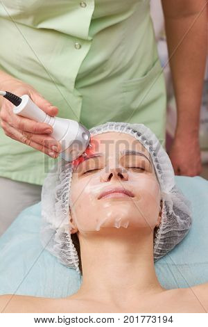 Radio frequency face lift. Young woman undergoing skin therapy.