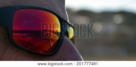 Curl Curl beach outdoor swimming pool reflected on a red sunglasses. Man in sunglasses with reflective seashore.