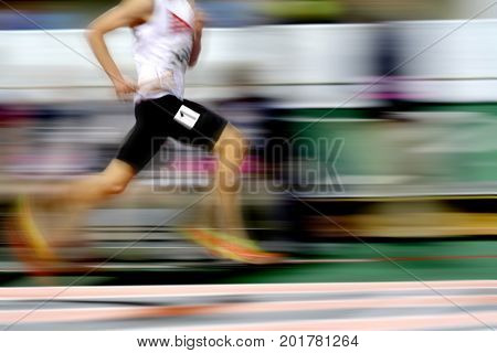 Runner running a race on track with baton relay for team score competition