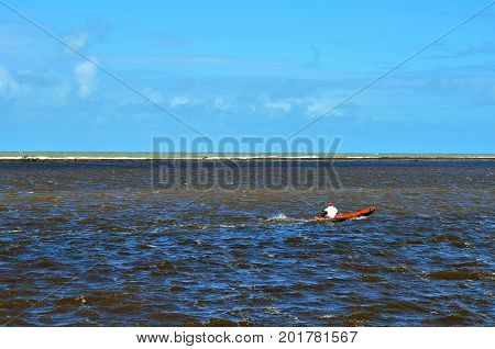 Small boat in the sea at river mouth protected by coral reefs in Porto Seguro, Bahia, Brazil. The sea in two colors separated by the coral barrier.
