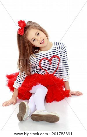 Portrait of a little girl in a bright red skirt with a red bow on his head.The girl sat down legs.Isolated on white background.