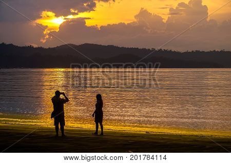 Kota Kinabalu,Sabah,Malaysia-Aug 8,2017:Silhouettes of couple enjoying beautiful sunset walk on the Likas Bay beach Kota Kinabalu,Sabah East,Malaysia Borneo
