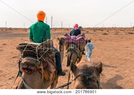 JAISALMER RAJASTHAN INDIA - MARCH 07 2016: Wide angle picture of local camel carrying tourists in Thar Desert located close to Jaisalmer the Golden City in India.