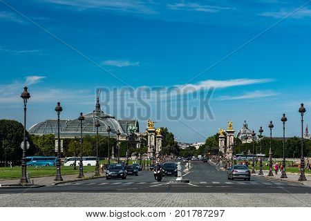 Paris France - August 14 2016: Cars and tourists on the Alexandre III bridge known for its golden statues with view of the big palace in the background.