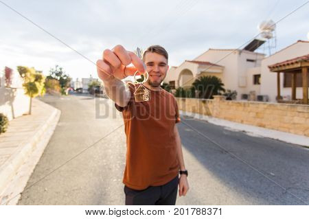 Property, ownership, new home and people concept. Cheerful young man holding house key