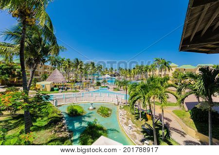 Cayo Coco island, Trip Cayo Coco, Cuba, July 11, 2017, gorgeous, amazing inviting view of hotel grounds, tropical garden and various swimming pools with people relaxing and swimming in background