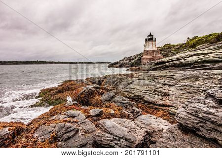 Castle Hill Lighthouse in Newport, Rhode Island, situated on a dramatic rocky coastline under a stormy sky