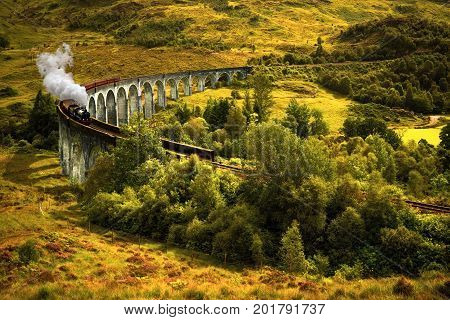 Jacobite steam train on old viaduct in Glenfinnan Scotland