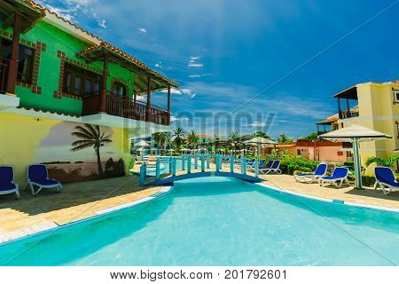 Cayo Coco island, Cuba, Colonial resort, July 16, 2017 beautiful amazing inviting view of swimming pool with stylish architectural buildings in background on sunny day