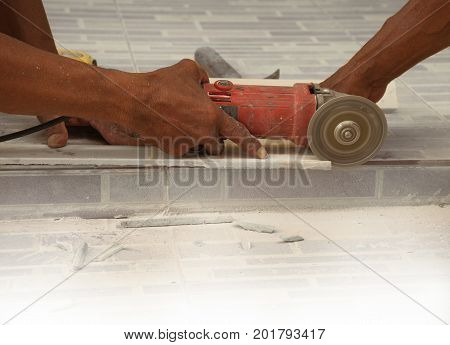 two bare hands of construction worker cutting ceramic plate with electric saw beware of occupational health