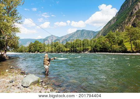 Fishing by flyfishing on the river. Russia Siberia. River Chelushman