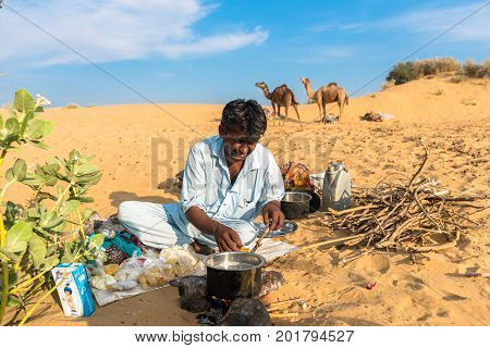JAISALMER RAJASTHAN INDIA - MARCH 07 2016: Horizontal picture of native indian man cooking in Thar Desert located close to Jaisalmer the Golden City in India.
