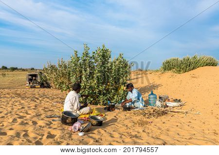 JAISALMER RAJASTHAN INDIA - MARCH 07 2016: Wide angle picture of native indian men cooking in Thar Desert located close to Jaisalmer the Golden City in India.
