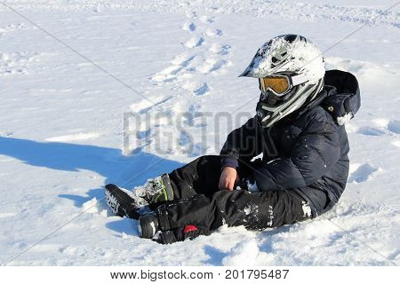 Child Wearing A Biking Helmet Sitting In The Snow