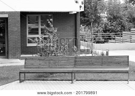 Park Bench In A Spring Garden. New Modern Courtyard.