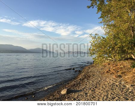 Scenic lake landscape view with rocky beach and waves on shoreline. Tree branches over rocky beach in foreground. Smoke on horizon over mountains with blue sky and white clouds background.