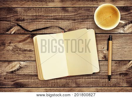 Top view on wooden desk with notepad pen and cup of coffee. Flat lay. Mock-up. Work background.