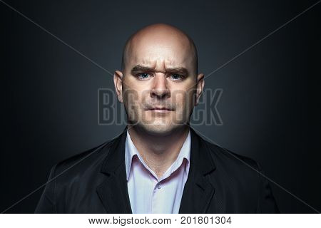 Portrait of a man with angry expression in dark