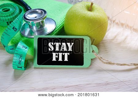 Stay Fit inscription written on wooden tag over fitness equipment and nutrition food.