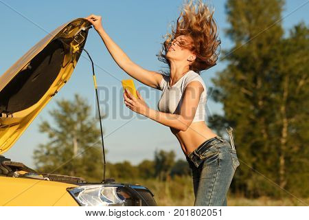 A young attractive girl opened the hood of the car and makes a video call on the cell phone. Trouble on the road. She is waiting for the tow truck