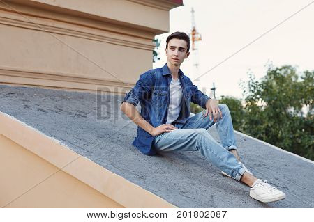 A young guy is sitting on the roof. He is wearing a jacket and jeans. Hipster city fashion.