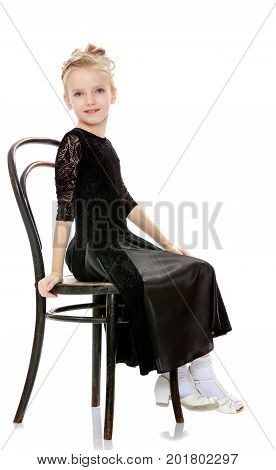 The slender little blonde girl dancer in the long dress of black color made specifically for performing .Girl sitting on an old Viennese chair and looking at the camera.Isolated on white background.