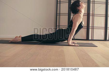 A young woman performing yoga-asanas in the hall. Urdhva mukha svanasana.
