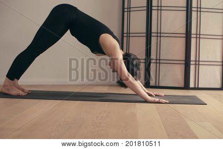 A young woman performing yoga-asanas in the hall. Artha mukha svanasana.