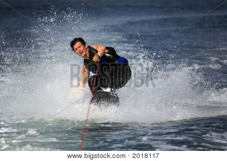 Sliding Wakeboarder With Strained Face And Closed Eyes In Water Splash