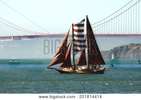 A large schooner sails toward the Golden Gate Bridge on San Francisco Bay. Its sails are full and all are bright maroon, with one red and white striped sail.