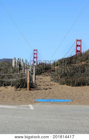 A sandy path leading from a parking lot over a short hill covered with iceplant  to see the entire Golden Gate Bridge.Just the top half of it shows from the start of the path. A rope fence goes alongside the path.
