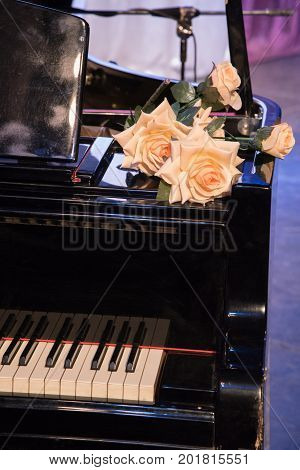 Large orange roses lie on a black old piano with white keys on the stage