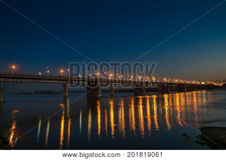 Bridge with bright lights across the wide river at night and reflection
