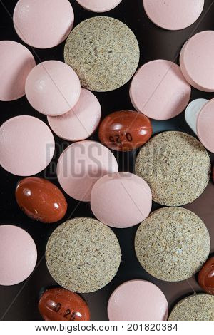 Top view of brown and pink painkiller tablets and pills