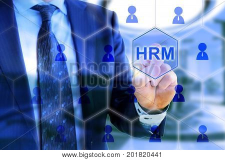Businessman in blue suit on office background touching HRM in a grid with people