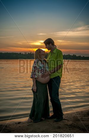A pregnant beautiful woman with her husband on the river bank beach smiling and touching her mehandi ornament belly with love and care. Happy couple, family relax on sunset