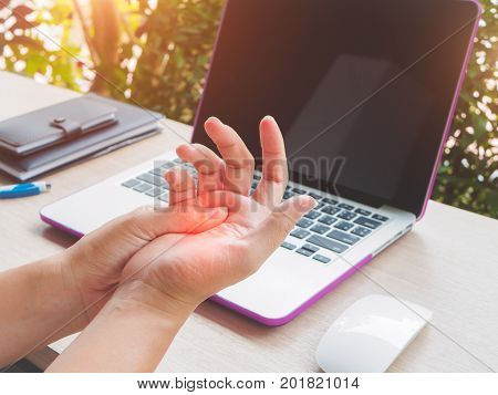 Closeup woman holding her painful hand from using computer. Office syndrome hand pain by occupational disease.